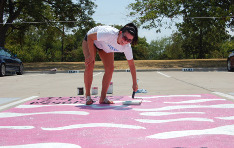 Students battle the heat to paint parking spots