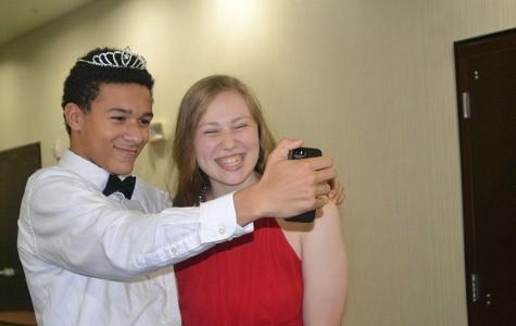 Take a selfie \\ Saber Team Commander Nick Mavis steals a selfie and a crown for a photo op with sophomore princess Ashley Henagin.