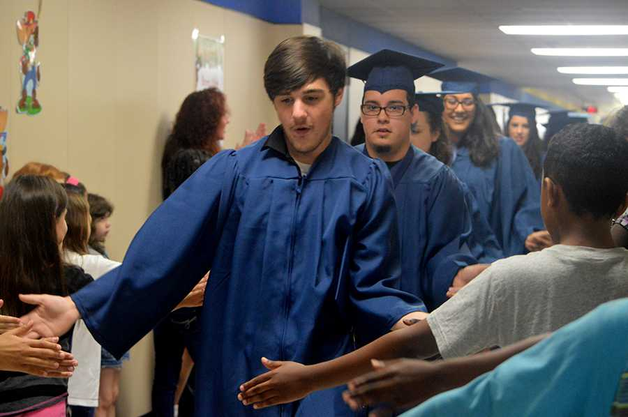 Hands in \\ Walking through his old elementary hallways, senior Tyler Lanier is congratulated by current Birmingham Elementary students. He was in a tragic car accident one day after graduating.