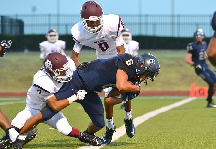 Getting past the goal line, senior Jared Wyatt scores a touchdown after catching a pass to take the 14-0 lead against the Red Oak Hawks. Varsity defeated Red Oak 49-7 at the season opener Aug. 28 at WISD stadium.