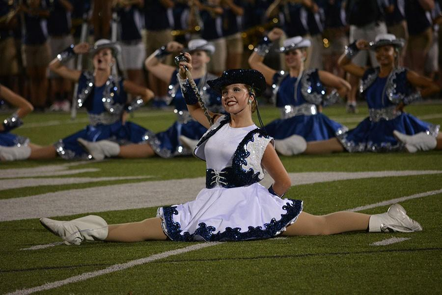 Got to split \\ Showing off the opening dance, senior Lieutenant Kaitlyn Smith smiles at the crowd before continuing the performance Sept. 10.