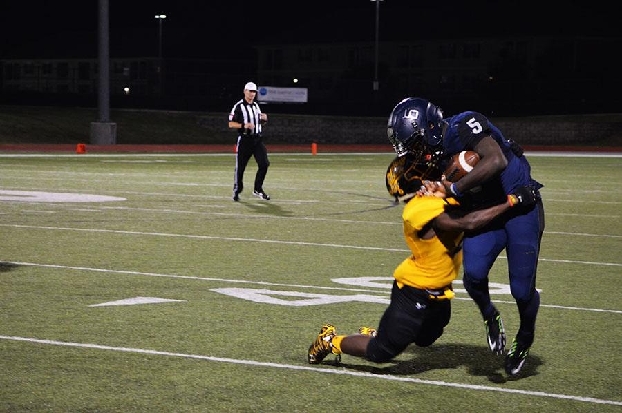 One on one // Getting taken down by a Yellow Jacket, junior Eno Benjamin gets thrown off the field after taking the ball halfway down the field Oct. 29 eventually leading the ball to the end zone giving varsity the lead 7-12.