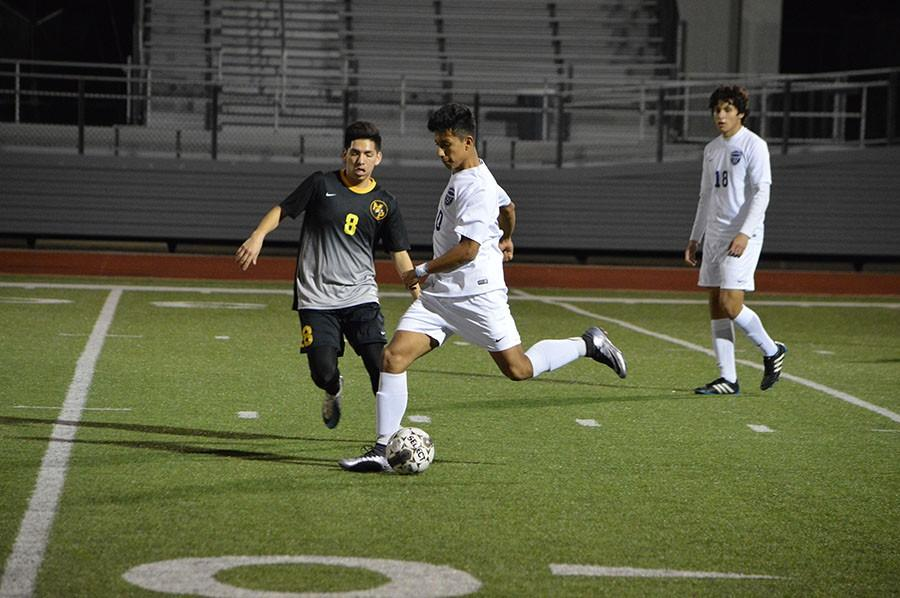 Keep away // Passing up the field, junior Mauricio Jimenez kicks the ball to get it down to a fellow teammate to try and score a goal Jan. 19. The team fell short 2-0 against Mount Pleasant at Wylie Stadium.