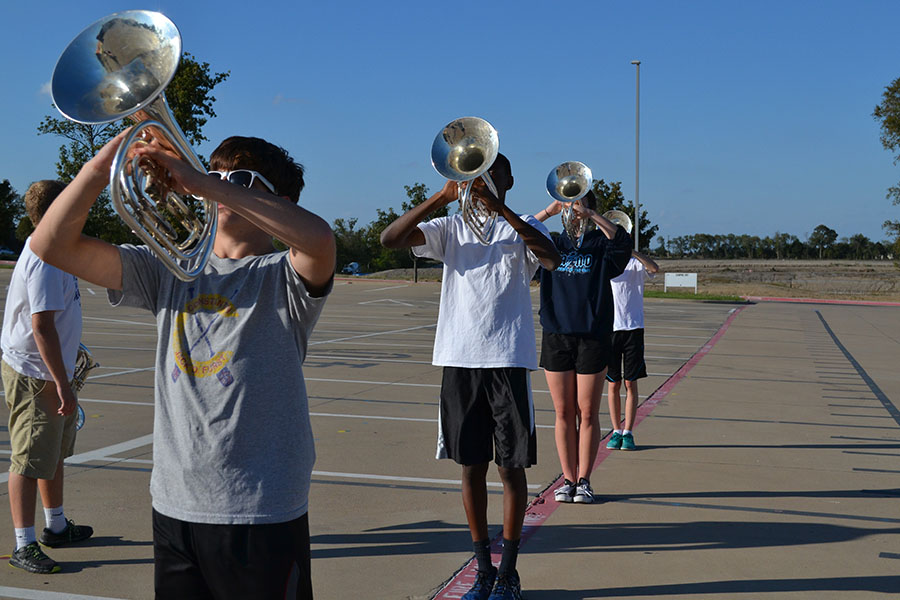 "Melodic mellos// Rehearsing marching fundamentals, junior Blake Taber adjusts his mellophone horn angle to the sky while playing the opener for the 2017-2018 marching show ""Through the Night"". Photo by Liz Harkins"