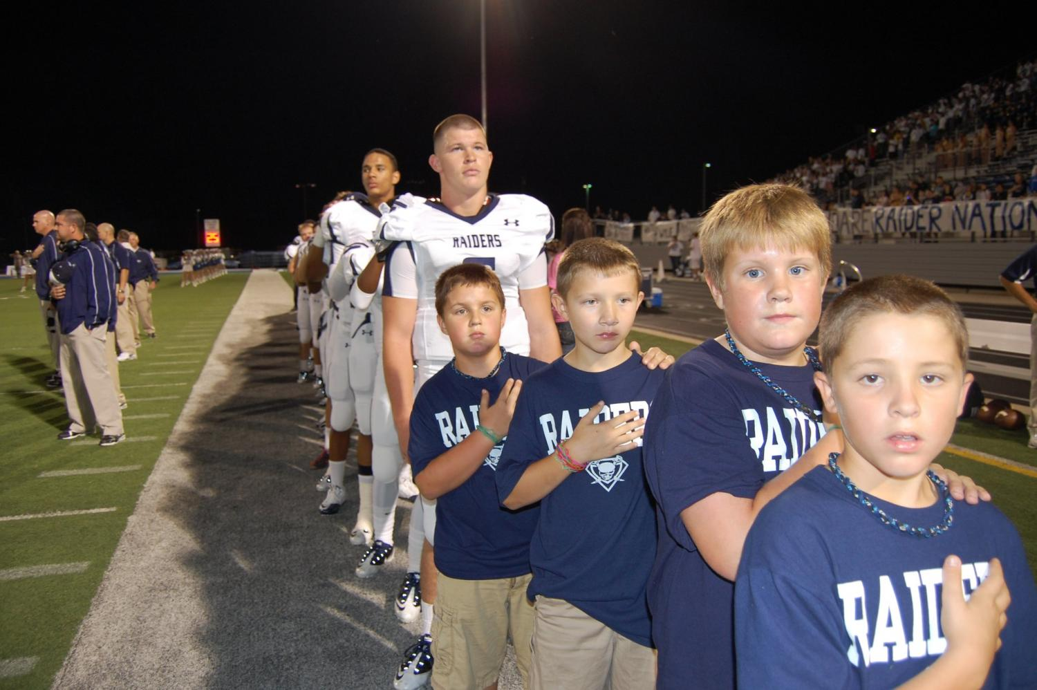 Raider for life // From the 2013 season, seniors Jesse Brubaker and Marcell Ateman stand behind ball boys Cooper Andrews, Tyler Lambert, Will McCune and Travis Lambert. The four ball boys are now students here.