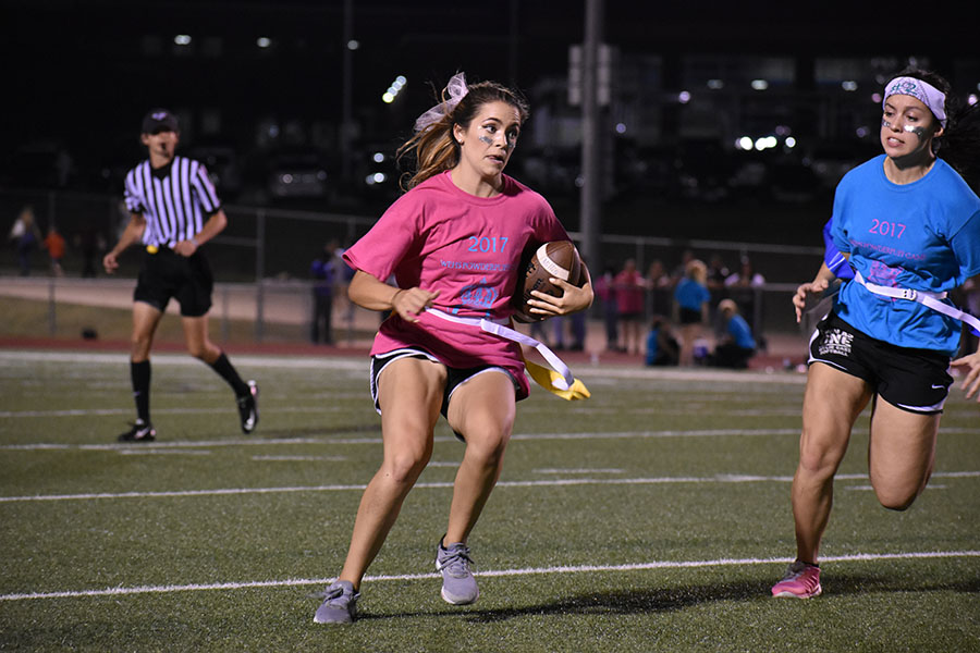 Break away \\ Rushing to the outside, senior Madison Dorethy looks to juke out senior defender Madison Donaldson in the first Powderpuff football game. The Blue Team defeated the Pink Team 16-11 Oct. 6.