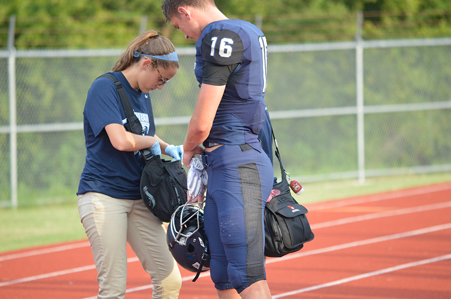 On and off // Junior Kelsey Pierce helps out football player Zachary Young on the sidelines during a Frisco Scrimmage Game. Photo by Whitney Tobias.