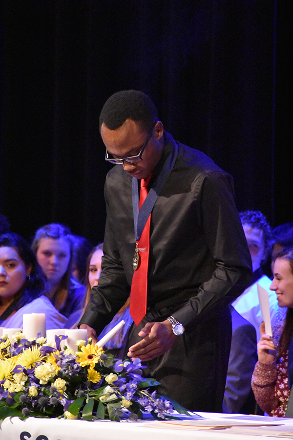Light it up // Lighting the candle, senior NHS president Obinna Ejikeme starts the NHS induction ceremony Oct. 30. NHS inducted a total of 94 new members. Photo by Harper Taylor