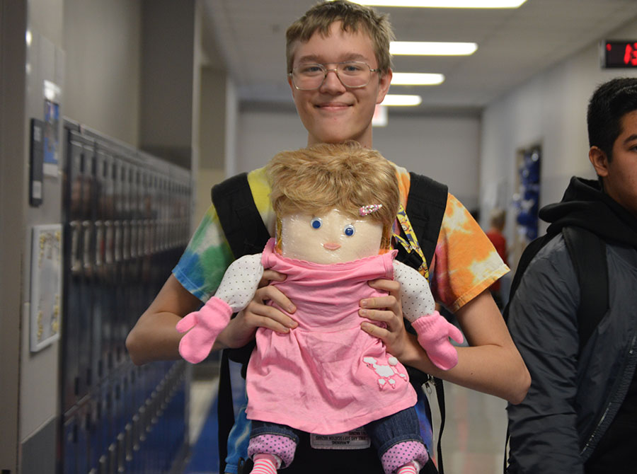 "Dress up // Walking through the halls, sophomore Edward Shuster carries around his flour baby during homecoming week Oct. 19. ""I named my baby Elenor because the name is like a female version for Edward,"" Shuster said. Shuster dressed up his baby for each spirit day Oct. 18 - 20 for homecoming week."