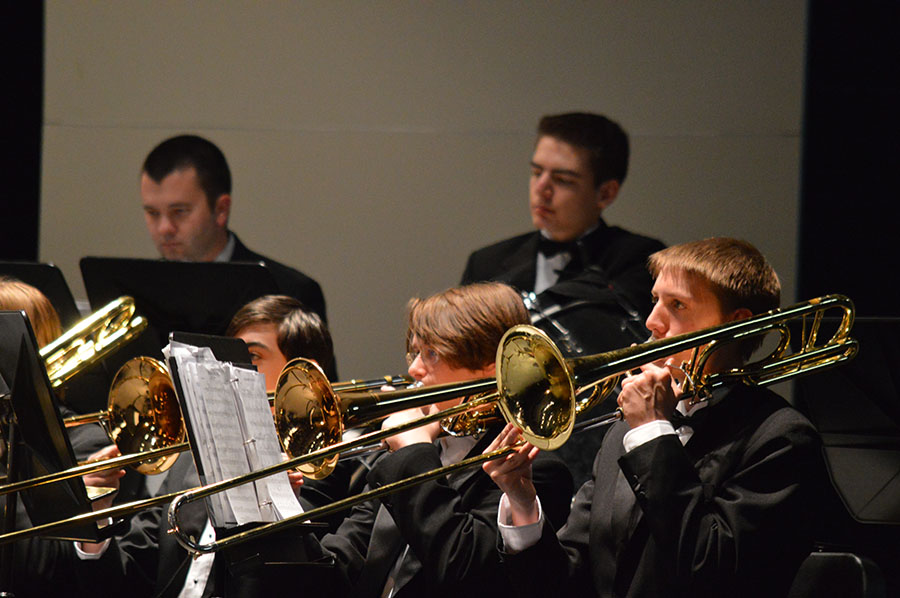 Summer dances // Playing the trombone, freshman Thomas Freeman looks up at the director to keep time. The Wind Ensemble played at the Mid Winter concert Feb. 13, preparing for UIL in March.