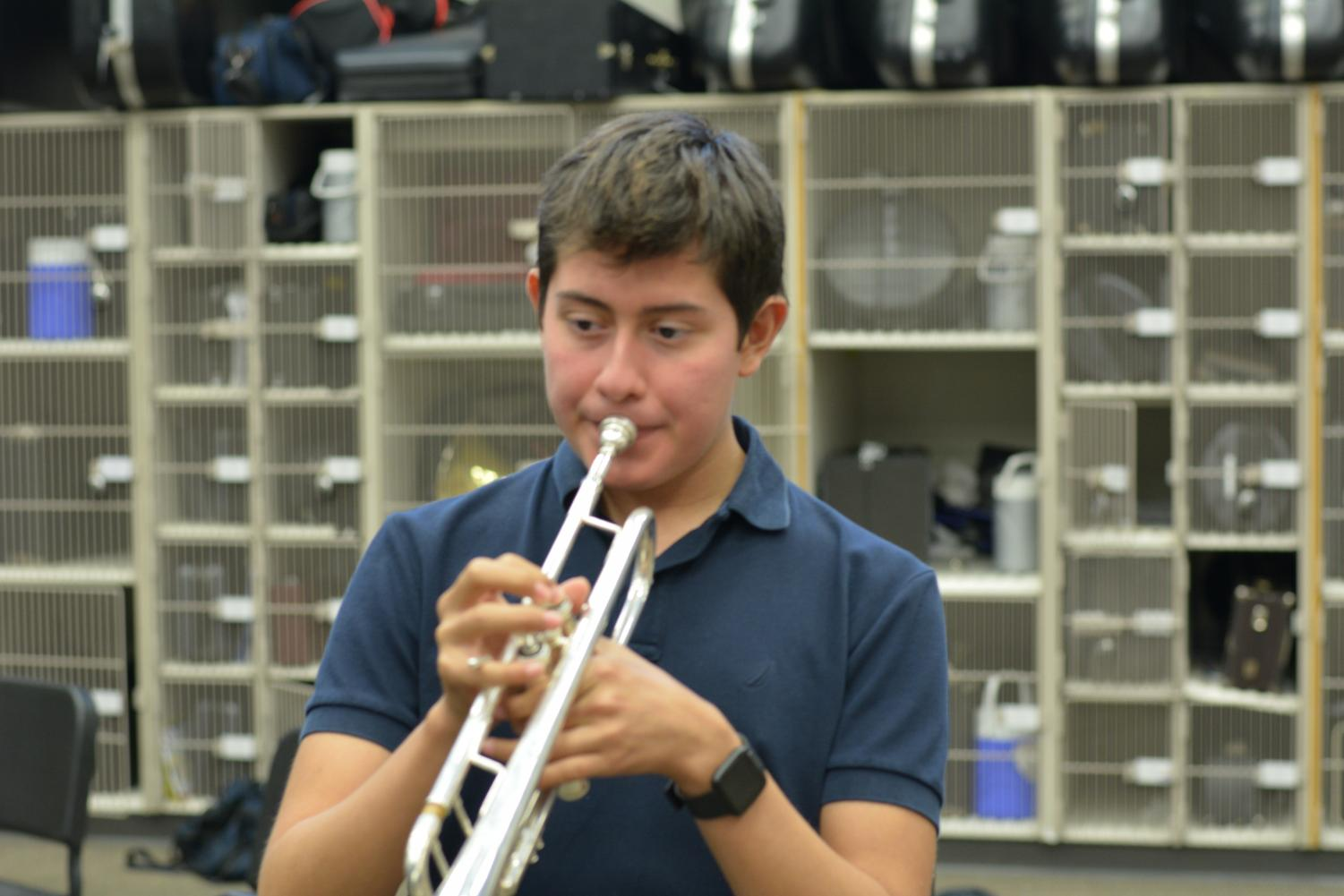 """Conquered notes \\  Focusing on his music, junior Ivan Najera plays a movement from his marching band show. The band's show this year is entitled Conquered featuring music from The Prince of Egypt and The Wind and the Lion. Najera missed over 60 days of rehearsal due to fighting cancer but still managed to learn the show music. """"I really enjoy playing music from movies I watched as a child, and it's a lot more fun than last year's,"""" Najera said."""