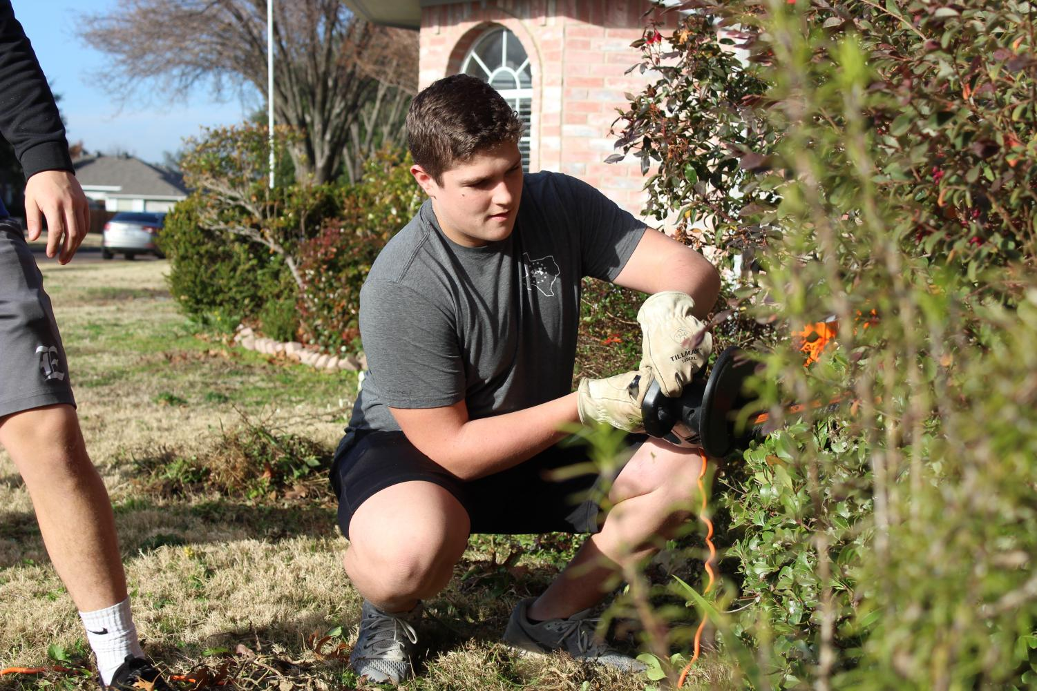 "Weed-eater // Senior Jacob Pryor uses an electric hedge trimmer to shape Mrs. Jennifer Holcomb's bushes. Mrs. Holcomb was recently diagnosed with cancer in her colon, back and liver. ""I was so touched at their generosity and outreach to me,"" Holcomb said."