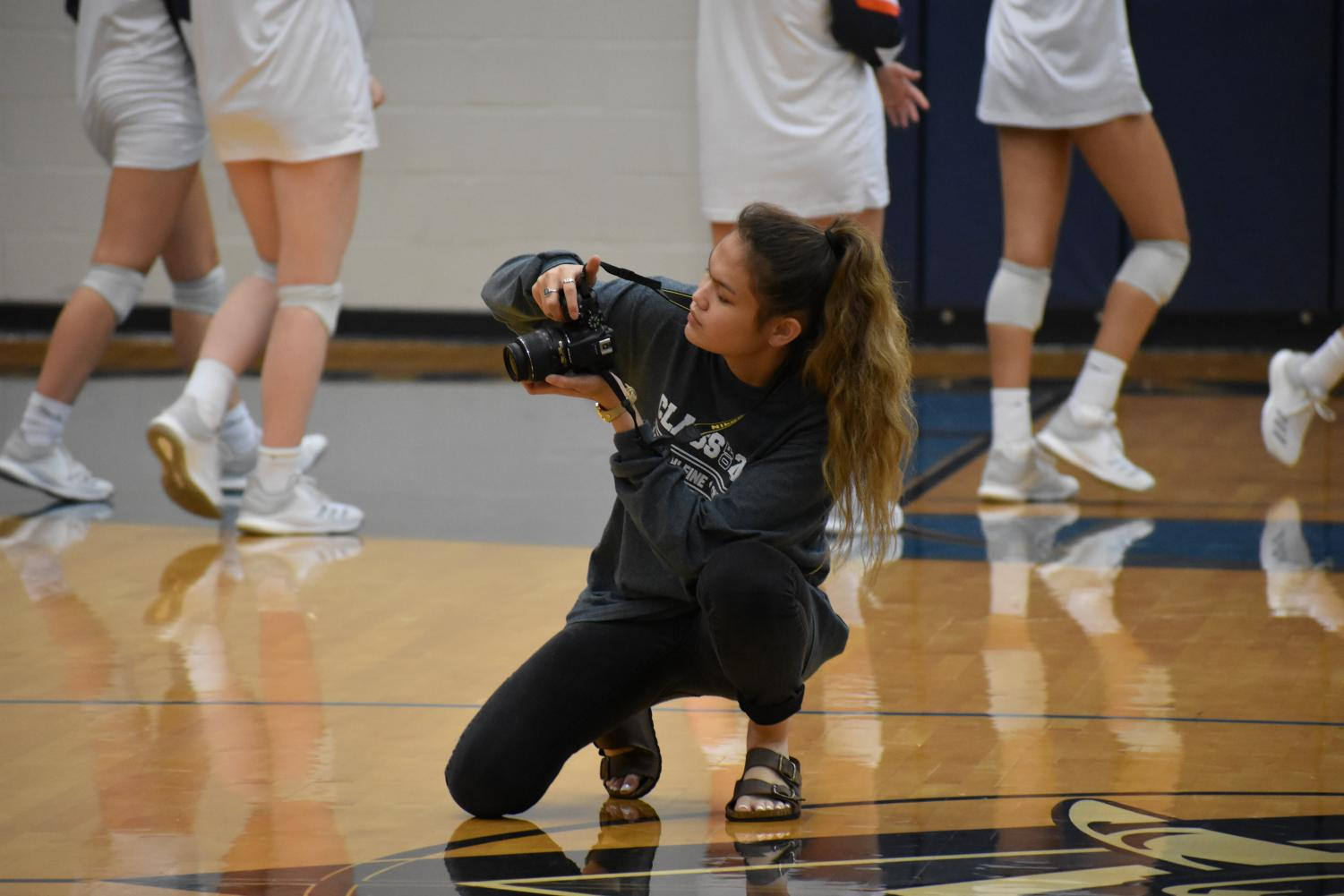 Triple threat \\ Senior Maddie Smith takes photos of a varsity volleyball game. She shares her work with The Wylie News, the school newspaper and yearbook because she is on all three staffs.