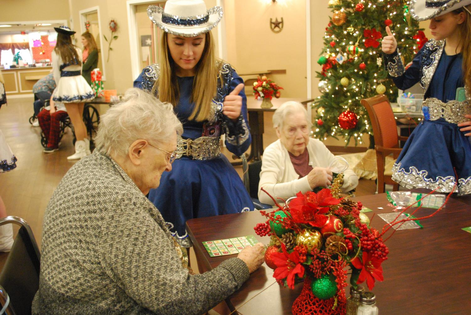 Season of service \\ Giving a thumbs up as her resident places her marker on the correct spot, sophomore Halli Fulton volunteers at Founders Plaza Nursing home along with the Sapphires for their service project. The drill team spent the day hanging out, singing Christmas songs, and handing out gifts to the residents there.