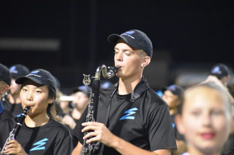 Fight to play \\ Senior clarinet player Aeyon Ko and bass clarinet player Wylie Dunham play the fight song during the pregame show in Mount Pleasant