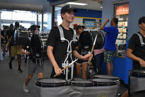 Drumming up support \ Entering the Wylie Walmart, senior percussionist Luke Enns plays the school fight song before ending the annual March-a-thon Sept. 7.