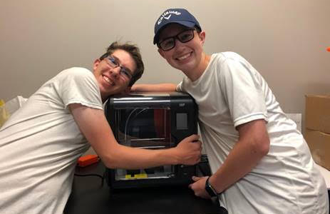 3D love \\ Senior Collin Kaiser and sophomore Cade Swanson celebrate their new 3D printer by hugging it in Mrs. Lawrence's engineering class.