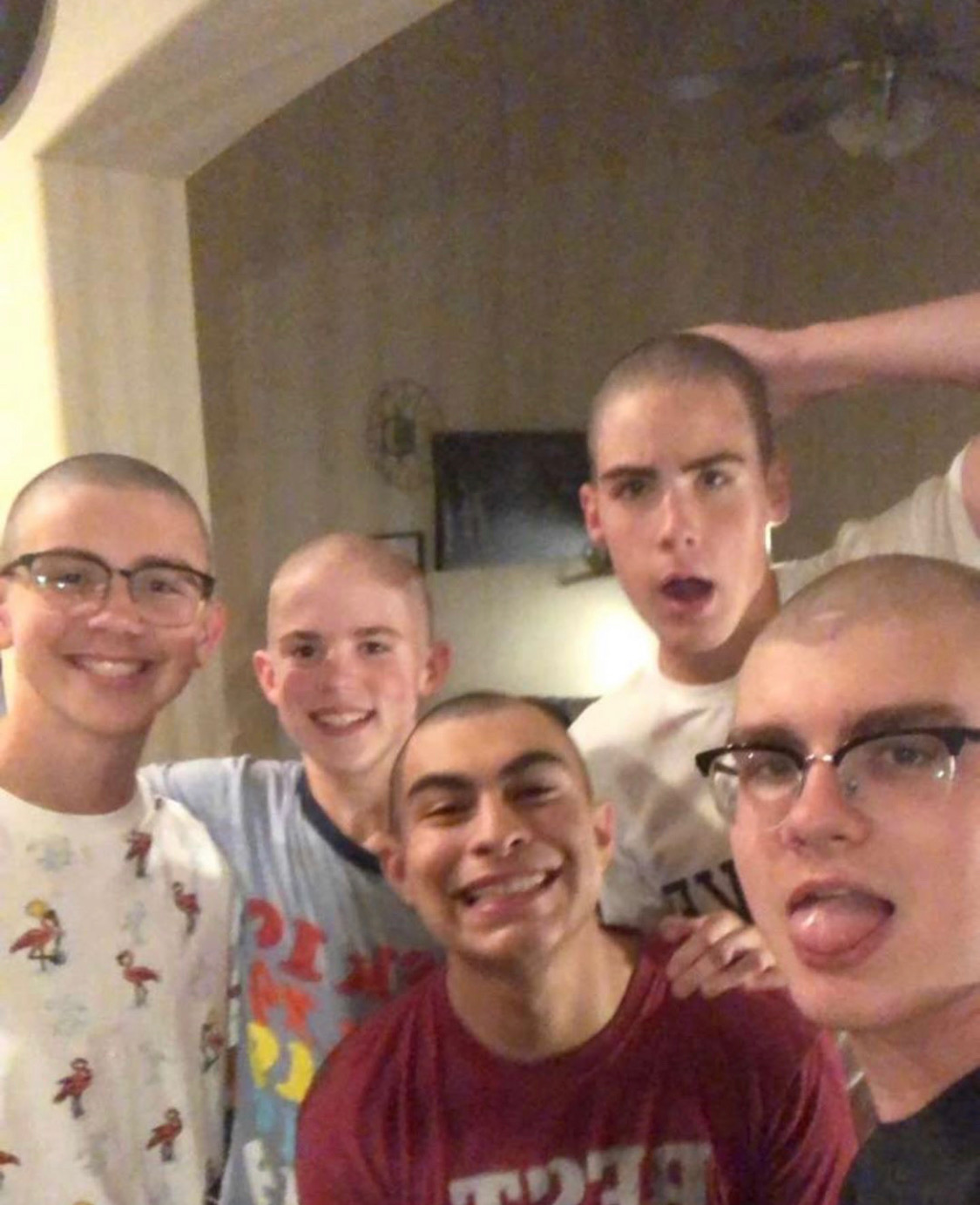 Snip snip \\ Posing their new looks, junior Hayze Gore (second from the left) and his four friends enjoy the feel of the fresh air on their heads after a new shave in support for their friend battling cancer.