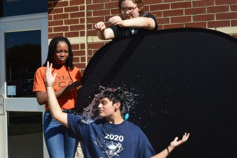 "Making a splash \ Dropping a water balloon, senior Emily Smalley saturates senior Sky Bese in Mrs. Gilpin's fifth period Photography II class. Students practiced adjusting their shutter speed to stop the motion of the water mid-air Oct. 21. ""It's fascinating. I"