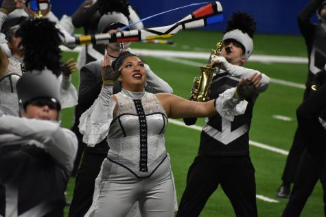 "Toss up\ Senior Stephanie Rodriguez tosses a rifle during the second movement, Mass Media, of the state-bound show entitled ""Massive."""