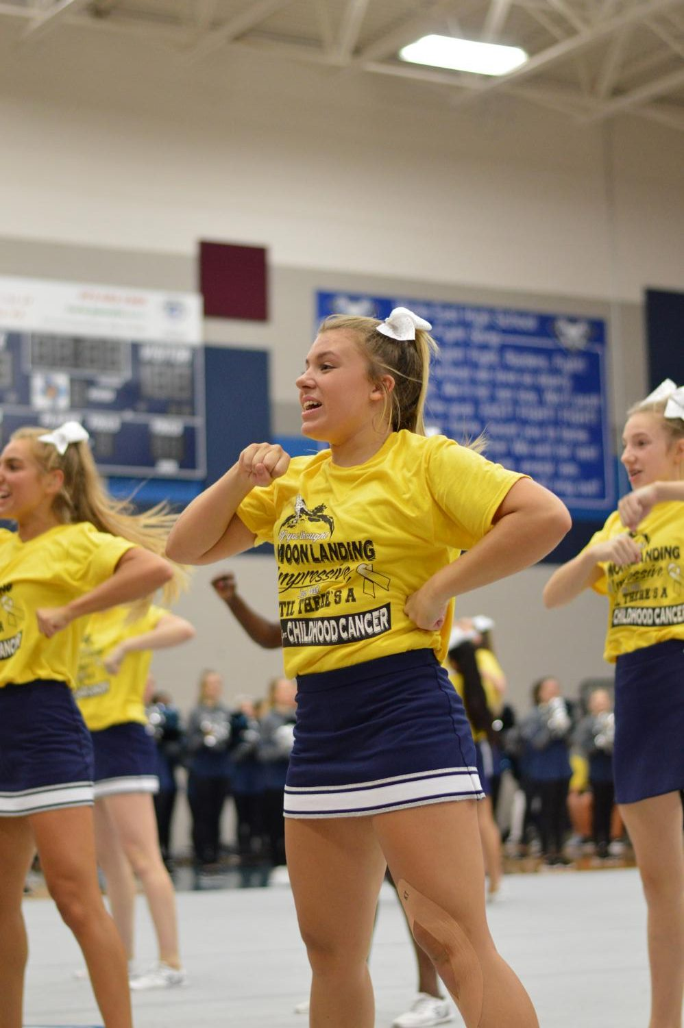 "Battle Cry \ Leading the crowd in a chant, sophomore Campbell Andrews shows her school spirit at the Gold Out pep rally Sept. 6. This is Andrews' first year on varsity cheer. ""I've grown so much as a person being on varsity,"" Andrews said."