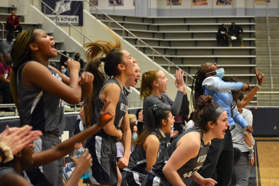 Scream team \\ Jumping up off the bench, the girls varsity basketball team cheers for their teammate Aleena Dawkins as she scores, to tie up their game against Red Oak high school Feb. 22. The team won their playoff game in overtime 65-60 Feb. 26.