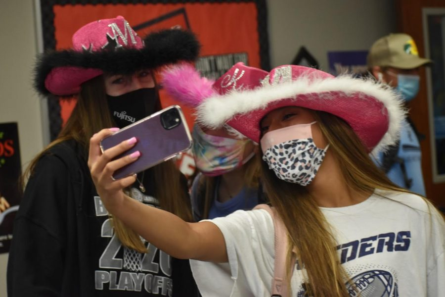 Spirit selfies \\ Displaying their festive hats, seniors Mya Jones, Morgan Healey and Kayla Green, take a picture with their pink, self-decorated cowboy hats to show their school spirit during the first spirit day of the school year, Hat Day, Aug. 21. Wylie High and East joined together for mutual commUNITY spirit days.