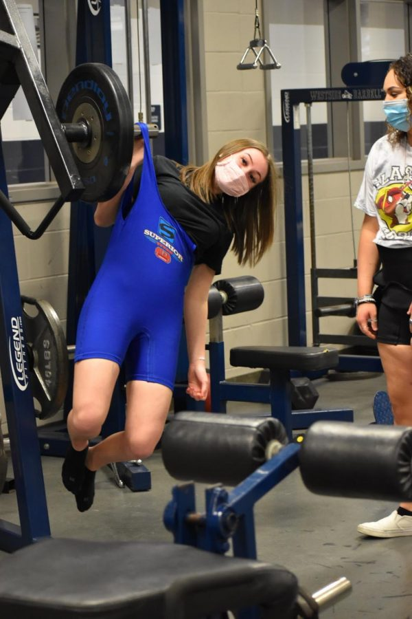 Hang in there \\ During morning practice, sophomore Raegan Smeltzer pulls up her deadlift suit by hainging on weight racks Feb. 23. The girls are preparing for their upcoming powerlifting meet.