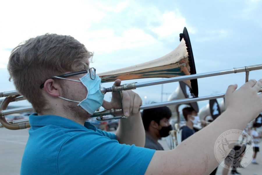 "A morning start \ Warming up for the morning marching band rehearsal, sophomore Daniel Aanerud prepares for the Pride of the East marching show, ""Hamilton"" Sept. 4."