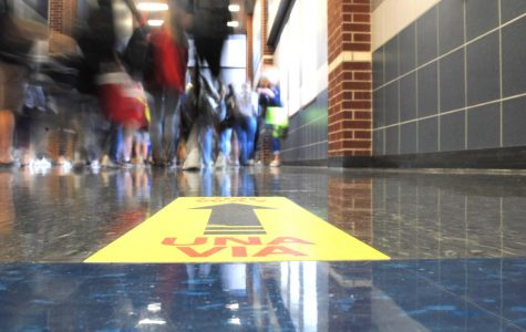 Footsteps // Students walk in the 800 hallway between fifth and sixth period Sept. 11. Signs on the floor and walls designate the direction students need to walk in as part of the new measurements to ensure social distancing.