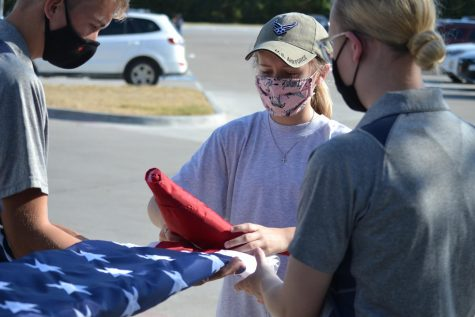 "Helping hand \ Guiding a first year, junior Riley Peirce and senior JT Red help guide freshman Karis Craig through the proper flag folding procedures during the end of the day flag ceremony Aug. 18. ""Folding the flags can be one of the hardest things to perfect, but once you got it you're gold,"" Red said."