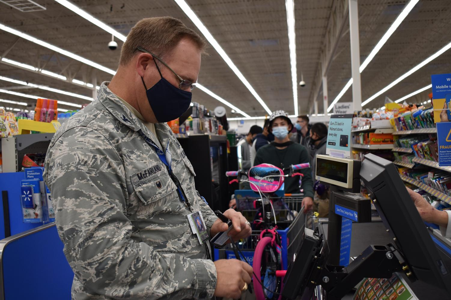 """JROTC is coming to town \\ Checking out at the Wylie Walmart Colonel Brooks McFarland shows JROTC the true meaning of Christmas. Every year, members of JROTC cadets go class-to-class collecting money from their peers and teachers to purchase gifts for the Wylie Way Christmas Angels. """"We were able to raise more money this year, which was really cool because we could give even more presents out,"""" C/1Lt TJ Garvin said."""