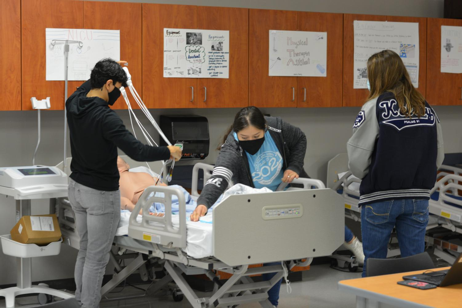 """Heartfelt Future // Practicing their lead placement for their EKG, senior Nancy Gomez, and other students prepare for their health care careers. """"I am really outgoing with people so working with different patients and people is interesting to me. I am planning to be a sonographer or an ultrasound tech,"""" Gomez said."""