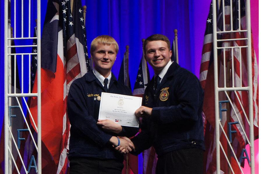 Brown earns his spurs \\ Accepting his degree, senior Dakota Brown is honored for his work in FFA during the 2014 Lone Star Degree Convention.