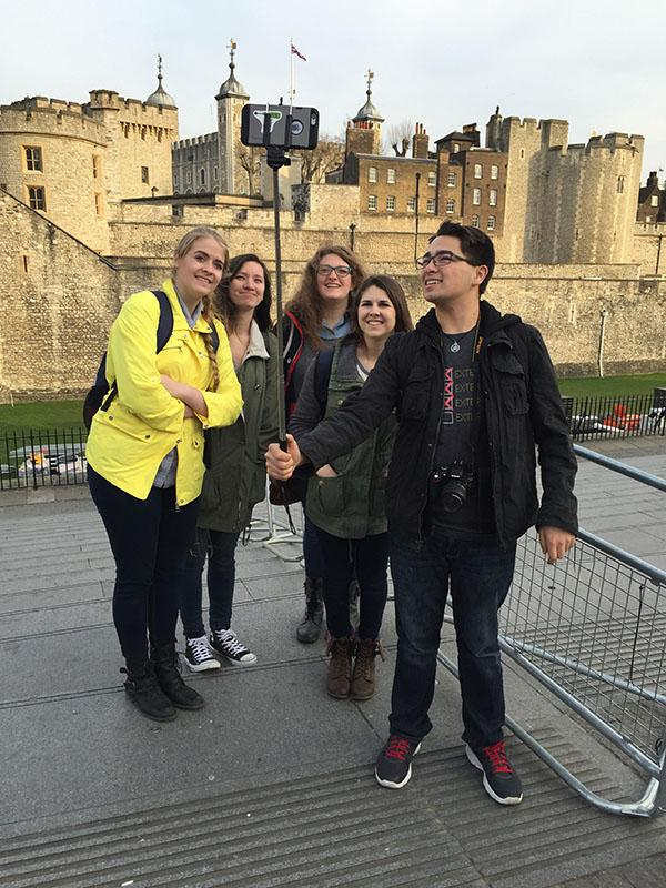 Terrible tower \\ With eyes turned up, junior Garrison Whadford holds up his selfie stick for a picture in front of the Tower of London. During the tour of the grounds, the students learned the gory history behind the castle from a Yeomen Warder, better known as a Beefeater.