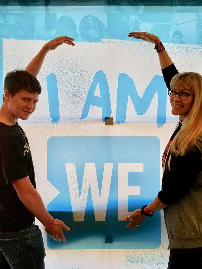 I am ready // Walking into the venue, sophomore Trevor Wischnewsky and Spanish teacher Mrs. Jamè Farrar stop to take a picture by the charities slogan. Wischnewsky was chosen to attend the WE charity-hosted event at the Curtis Culwell Center in Garland, Texas March 21.