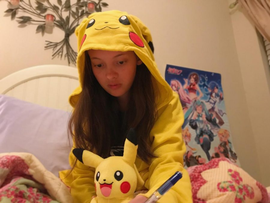 Athena // Huddled in bed with her favorite Pokémon jacket and plushy, junior Athena Ensign completes her physics homework.