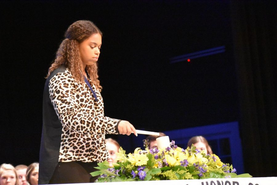 """Light the world // Illuminating the stage, treasurer Nia Carter lights one of the candles that represent the pillars of NHS at the induction ceremony Oct. 30. """"The pillars are characteristics of a dedicated student that pushed themselves to achieve high goals,"""" Carter said."""