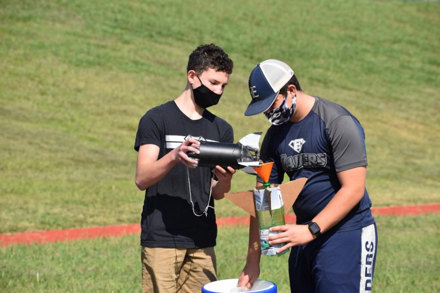 """Lift off \\ Freshmen Brayden Tran and Nate Guynes fill their home-made bottle rockets with water. """"Making the bottle rockets took a lot of time and effort,"""" Tran said."""