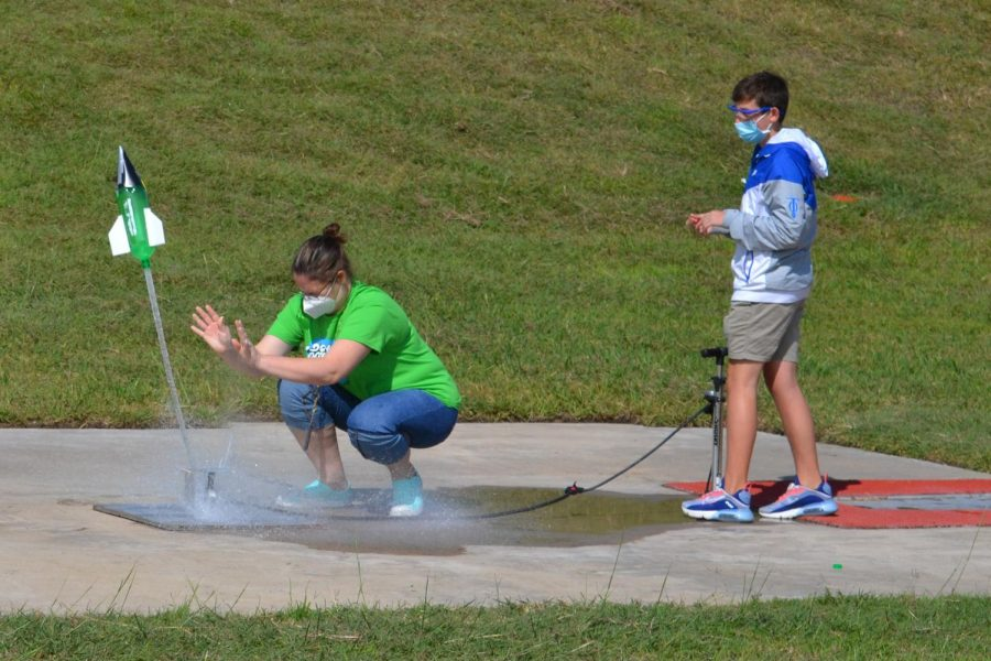 """Prepare for lift off \ Engineering teacher Ms. Lauren Plunk secures a bottle rocket to the launcher as freshman Evan Autrey applies pressure with a bicycle pump Sept. 25. """"The bottle rocket experiment was fun and a great start to the school year,"""" Autrey said."""
