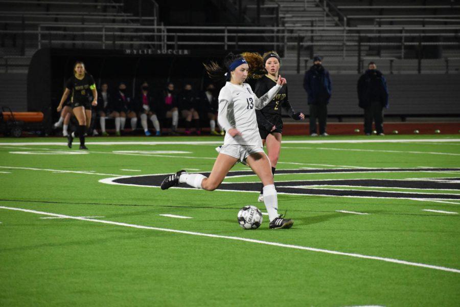 Kickin it \\ Stealing the ball from the Bulldogs, senior Sarah Satterwhite passes it to her teammate. Girls varsity soccer won against Royse City 4-0 Jan. 8.