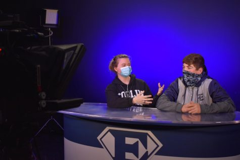 """On air \\ While talking to the camera in front of them, junior Jayden Thompson and sophomore Knox Wilson read off of a teleprompter. """"These episodes are produced for the students to watch to let them know whats going on around them,"""" Thompson said. There are usually different anchors each time an episode is filmed."""