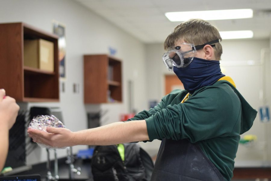"""Burst your bubble \\ Sophomore Bret Tomaszewski prepares to have the butane gas-filled bubbles in his hands lit by Miss Molly Brinkley in her fourth-period chemistry class Dec. 3. """"My favorite part of chemistry is getting to do the labs,"""" Tomaszewski said."""