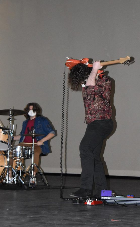 """Drummin it out \\ Playing the drums for his band Triple Forte, senior Aiden Klutts performs a Jimmy Hendrix song with his bandmate at the talent show. """"It was our first time  performing in front of a crowd like that, so it was a killer time for sure,"""" Klutts said."""