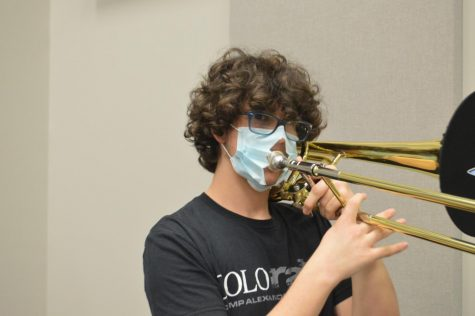 """Making music \\ Improvising, sophomore Jeremy Kvale performs a solo on the Bass Trombone for the Jazz piece: Chili Today, Hot Tamale Nov. 5. """"My favorite part about Jazz Band is everything, but especially playing low notes really loud and playing basslines,"""" Kvale said."""