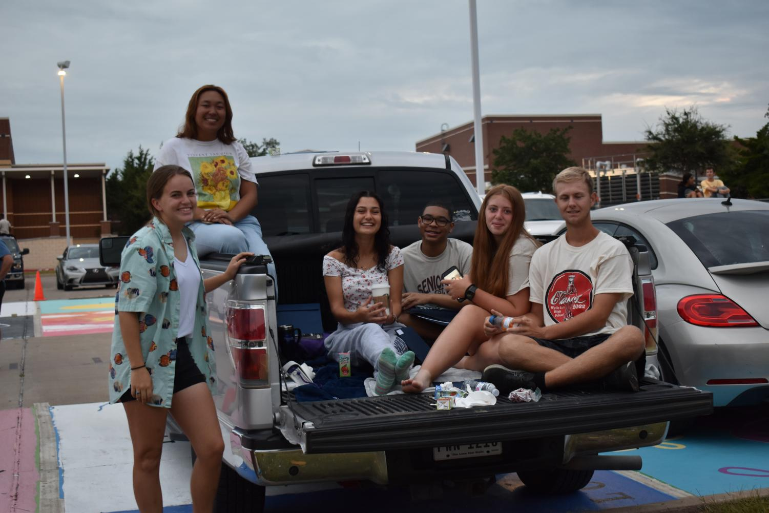 Rise and Shine \\ Enjoying snacks and each others company, class of 2022 meets in the parking lot to watch the sunrise at the Senior Sunrise Aug. 15.  Senior sunrise to me represents the beginning of a new chapter in our lives, senior Bailey Causey said. This year will be totally different from all the others, and it was fun to have a celebration to kick it off.