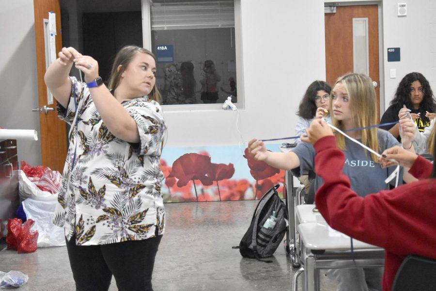 """Keeping mum \\ Agriculture teacher Ms. Valerie Turner explains how to create braids for mums in her floral design class. """"It was very fun to get to make a mum and experience it and the process of making one was super cool,"""" freshman Marisol Ruiz said."""