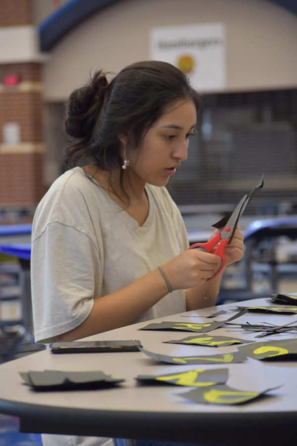 """Hoco prep \\ Preparing for homecoming week, senior Arely Sandoval decorates Student Council's wall. """"I had a lot of fun helping set up the background as well as the arrivals/departure signs,"""" Sandoval said. Especially because it is my last year being able to do it."""""""