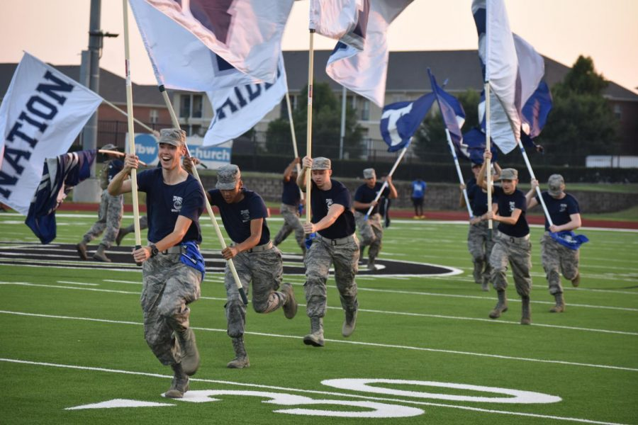"""Running the flags \\ After the football team scored a touchdown at their home stadium, the JROTC spirit team runs the big Raider Nation flags across the field. """"Spirit Team is always a good way to create fun and memorable experiences,"""" spirit team commander Hanah Robertson said. """"Personally, my favorite happened this past game in Longview. After halftime, we got up the Raider inflatable flawlessly. The amount of pride I had in my team was overwhelming."""" The spirit team hypes up the crowd at every football game."""