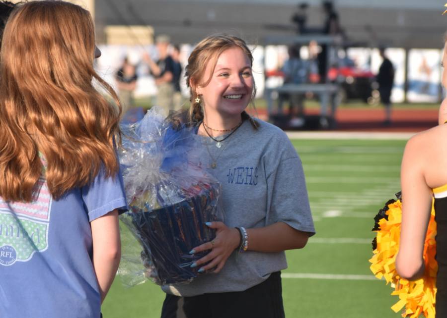 Behind the gift \\ Accepting the opposing team's student council gift, senior Ryah Hill shows off the gift from Mt. Pleasant at the varsity football game Aug.26.